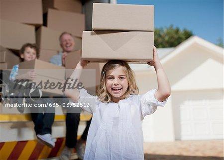 Fille portant des boîtes sur la tête de camion de déménagement