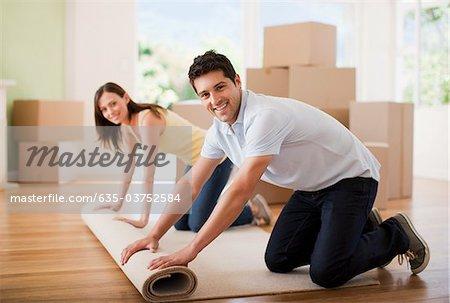 Couple tapis déroulant dans maison neuve