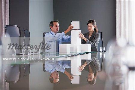 Geschäftsleute im Konferenzraum Würfel Stapeln