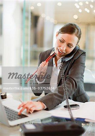 Femme d'affaires, manger des sushis et travaillant au bureau