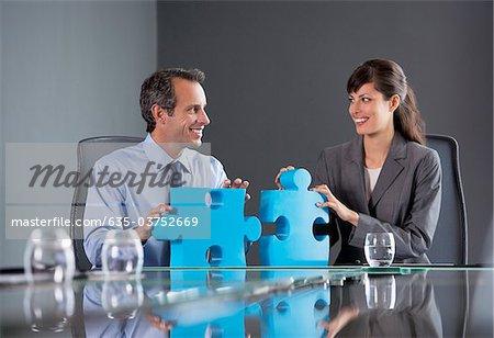 Geschäftsleute im Konferenzraum mit Jigsaw Puzzle-Teile