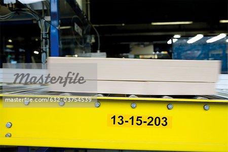 Boîte en carton se déplaçant le long de la bande transporteuse en fabrique de dalles de moquette