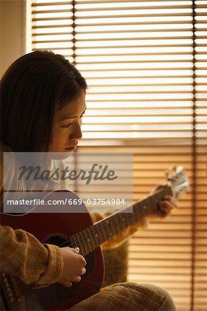 Eine Frau, die Gitarre zu spielen