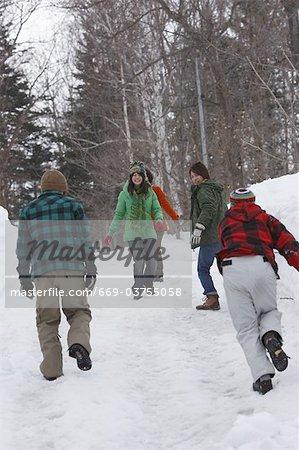 Junge Menschen gehen auf die verschneite Straße