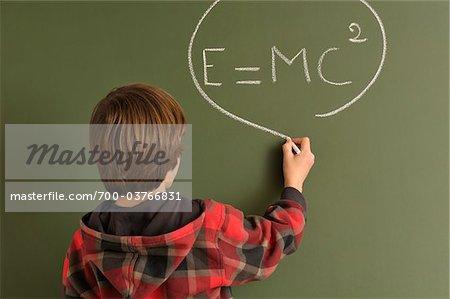 Boy Writing Equation on Chalkboard