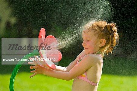 Girl Playing with Flower Sprinkler, Salzburg, Austria