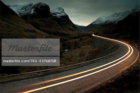 Trail of Car Lights at Dusk Through Mountainous valley, Glencoe, Scotland