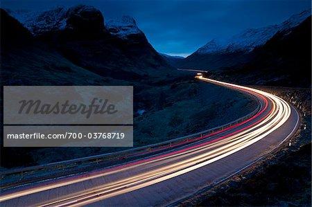 Trails of Car Lights at Dusk through Mountainous Valley, Glen Coe, Scotland