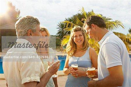 Groupe de personnes prenant un verre au bord de piscine