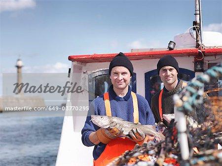 Pêcheurs sur le bateau de pêche avec des poissons