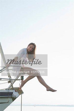Fille assise sur l'avant du bateau