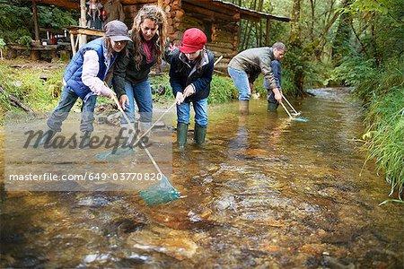 Familie Fischerei mit Netzen in einem Fluss