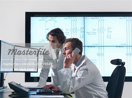 Wissenschaftler mit Diagrammen auf Bildschirmen
