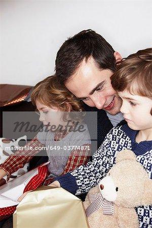 Mann mit zwei Kindern Geschenke zu öffnen