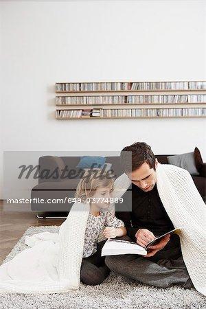 Vater und Tochter unter Decke
