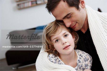 Père et fille câlins sous couche