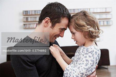 Fille boutonnant chemise de pères