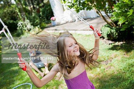 Jeune fille sautant à la corde dans le jardin