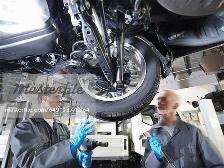 Mécanicien travaillant sous la voiture