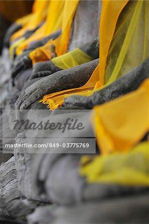Gros plan des mains de Pierre Bouddhas au pied du Temple Wat Yai Chaya Mongkol, Thaïlande