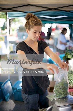 Woman Bagging Green Beans at Farmer's Market