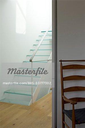 Verre de roulement cage d'escalier et chaise dans une maison victorienne, Wandsworth, Londres. Architectes : Luis Fernandez de Treviño
