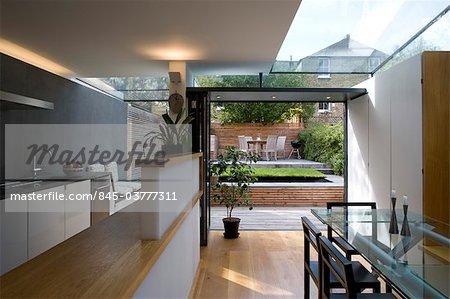 Cuisine moderne et salle à manger en regardant à travers le jardin dans un style victorien terrasse, Wandsworth, Londres. Architectes : Luis Fernandez de Treviño