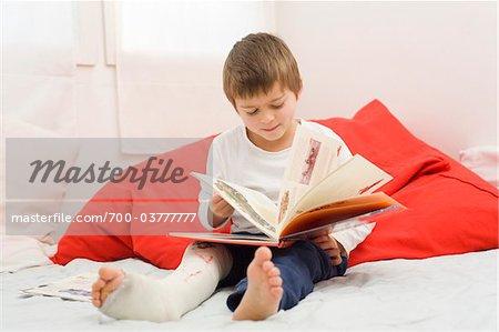 Garçon avec Cast sur jambe lecture livre