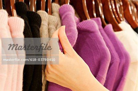 Main toucher pull en cachemire sur rack de vêtements