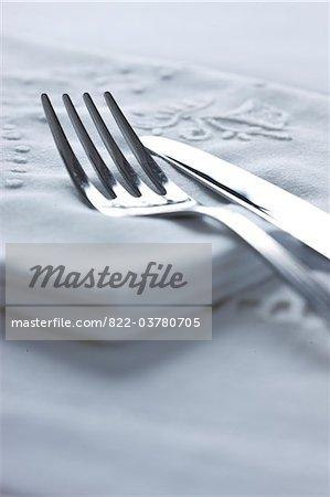 Messer und Gabel auf bestickten Stoff-Serviette