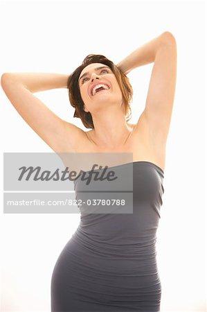 Lächelnde Frau mit Arme über Kopf verschränkt