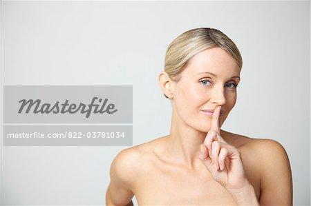 Doigt de femme tenant en face de lèvres
