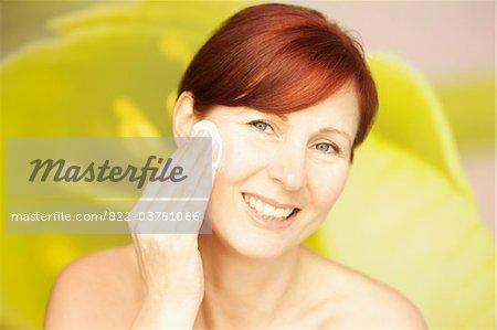 Femme souriante, à l'aide de coton sur le visage