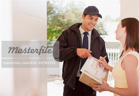 Femme signature de réception de la boîte pour le livreur
