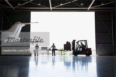 Arbeitnehmer, Boxen und Gabelstapler im hangar