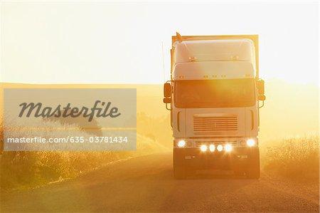 Semi-truck driving in dirt road
