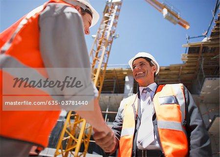 Travailleurs de la construction lui serrer la main sur le chantier