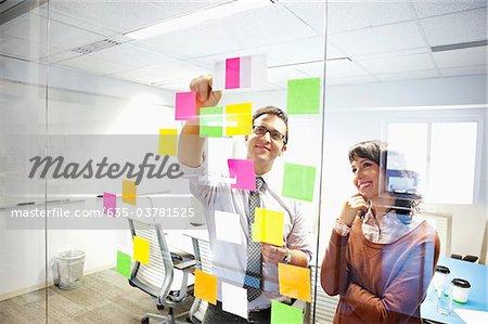Gens d'affaires en regardant les notes adhésives dans la salle de conférence