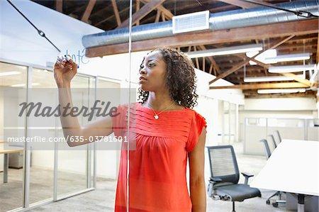 Femme d'affaires d'écriture sur le mur de verre de mur de conférence