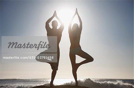 Paar üben Yoga am Strand