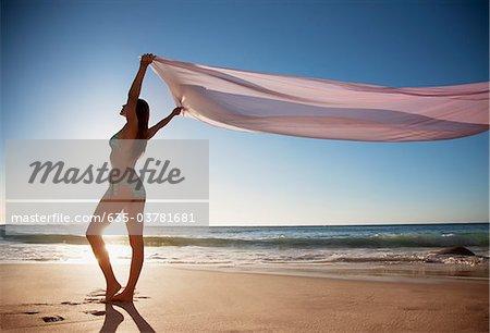 Femme debout sur la plage avec le tissu
