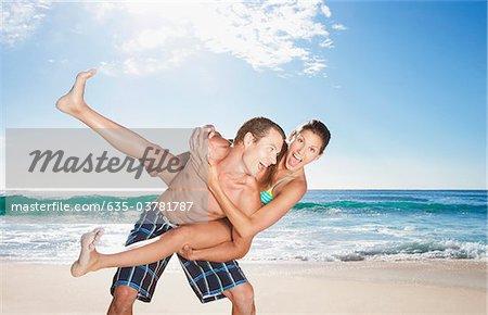 Playful man giving girlfriend piggyback on beach