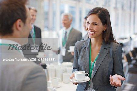 Femme d'affaires, boire du café et de parler à la collègue de travail
