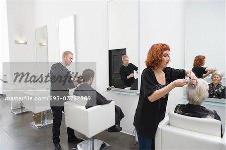 Stylistes coupaient les cheveux des clients au salon unisexe