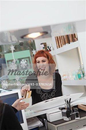 Propriétaire / réceptionniste prend le paiement dans le salon de coiffure