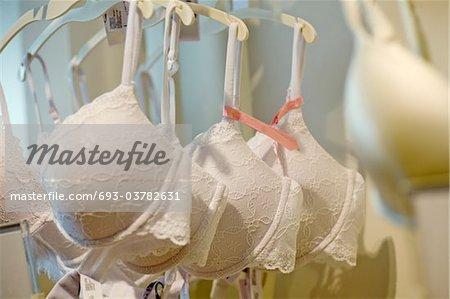 Ladies underwear on hangers. White bras with lace detail