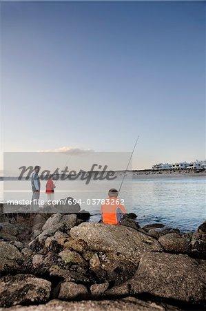Père avec deux soleils de pêche sur la plage Paradise de Langebaan, Afrique du Sud