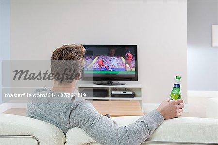 Junger Mann gerade Fußball im Fernsehen mit Bierflasche