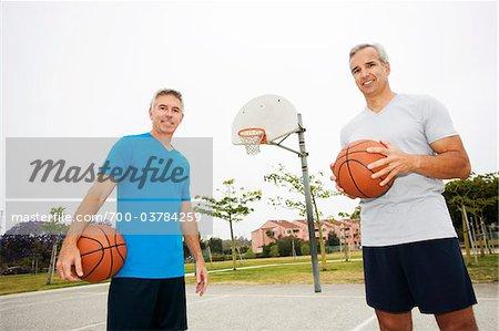 Zwei Männer halten Basketbälle auf Basketballplatz