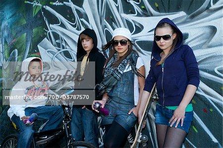 Groupe de jeunes adolescents debout devant le mur couvert de Graffiti